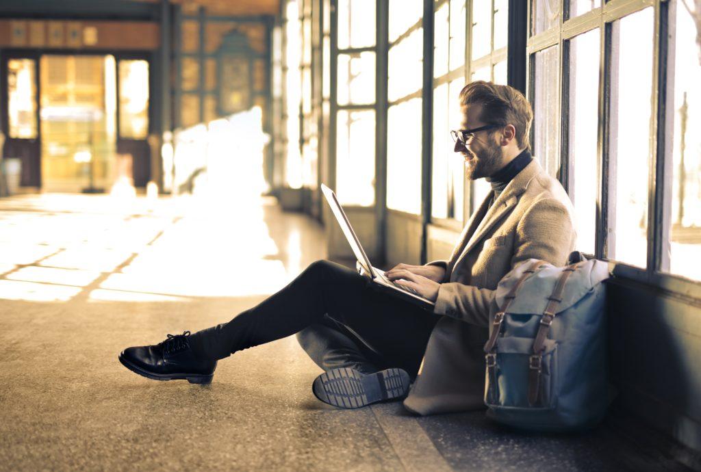 man wearing gray blazer working on laptop