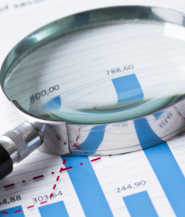 Magnifying glass and documents with analytics data lying on table