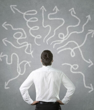 Confused, young businessman looking at many twisted arrows on the wall. Career decisions.