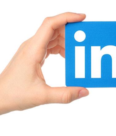 Hand holds Linkedin logo sign printed on paper on white background.
