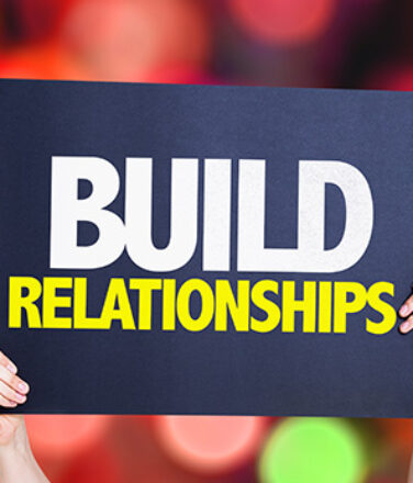 Hands holding up sign saying Build Relationships. Representing netowrking.